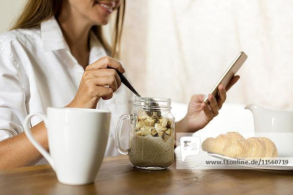 Frau am Frühstückstisch mit dem Handy