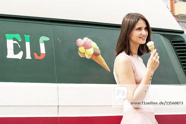 Lächelnde junge Frau mit Eistüte vor dem Eiswagen
