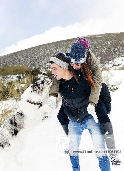 Junger Mann trägt sein Mädchen im Winter gebratenes Huckepack
