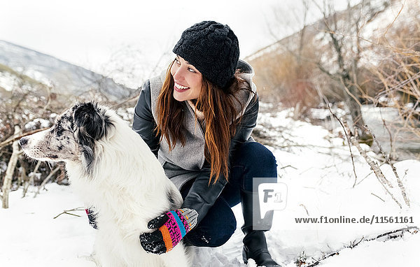 Junge Frau spielt mit ihrem Hund im Schnee Junge Frau spielt mit ihrem Hund im Schnee