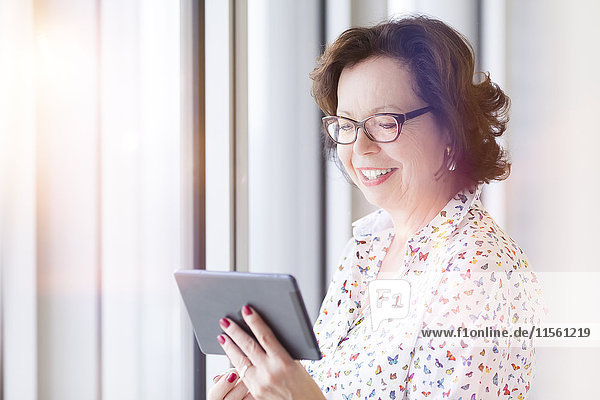 Lächelnde Senior-Geschäftsfrau hält Tablette am Fenster