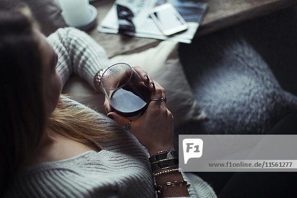 Junge Frau mit einem Glas Kaffee entspannt auf der Couch zu Hause