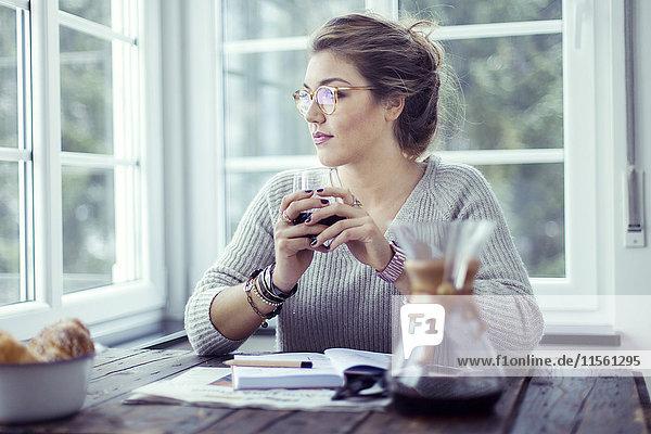 Junge Frau beim Kaffeetrinken am Tisch mit Blick durchs Fenster