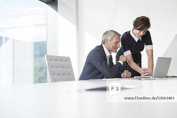 Geschäftsmann und Geschäftsfrau nutzen gemeinsam Laptop im Büro