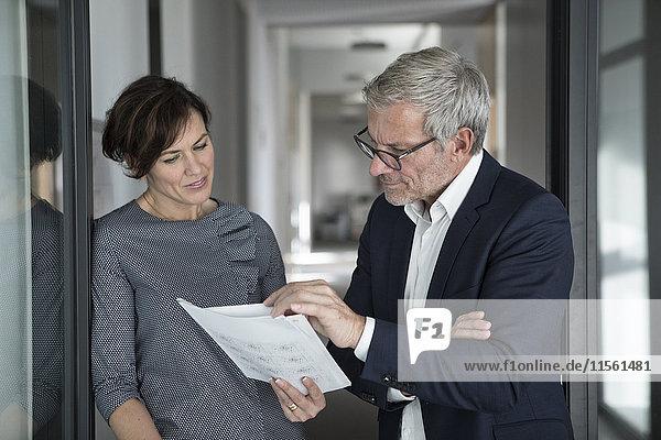 Geschäftsmann und Geschäftsfrau besprechen Dokument im Büro