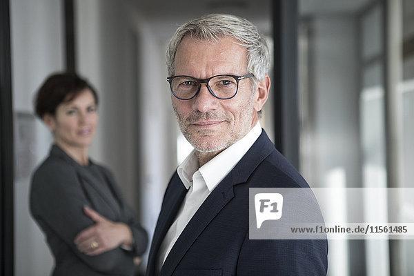 Porträt eines selbstbewussten Geschäftsmannes mit Unternehmerin im Hintergrund
