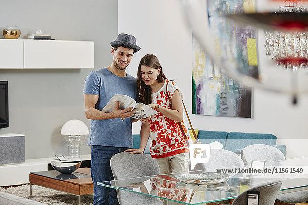 Paar im Möbelhaus mit Blick auf Esstisch  Blick auf Katalog
