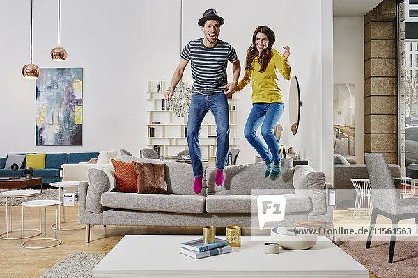 Paar im modernen Möbelhaus springen auf der Couch Paar im modernen Möbelhaus springen auf der Couch