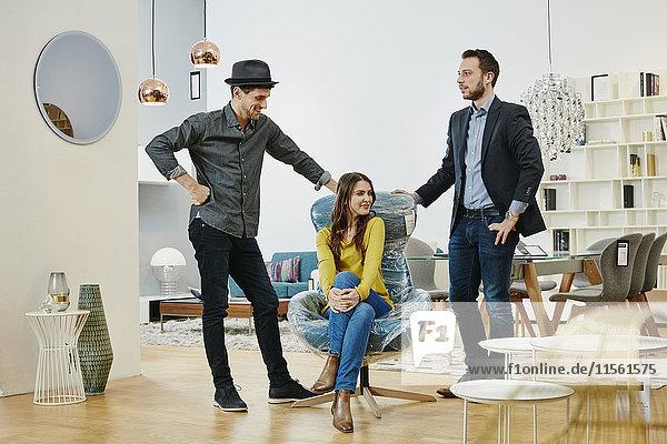 Frau im neuen Sessel im Möbelgeschäft  Mann und Verkäufer stehen neben ihr Frau im neuen Sessel im Möbelgeschäft, Mann und Verkäufer stehen neben ihr