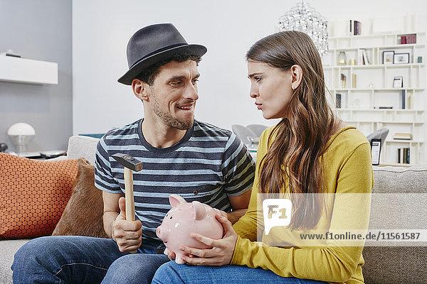 Paar im Möbelhaus beim Abbruch des Sparschweins