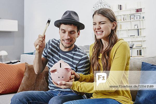 Paar im Möbelhaus beim Abbruch des Sparschweins Paar im Möbelhaus beim Abbruch des Sparschweins
