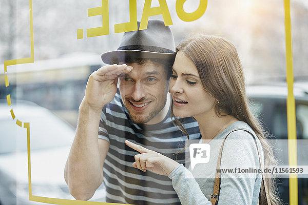 Junges Paar schaut durch das Fenster eines Coffeeshops