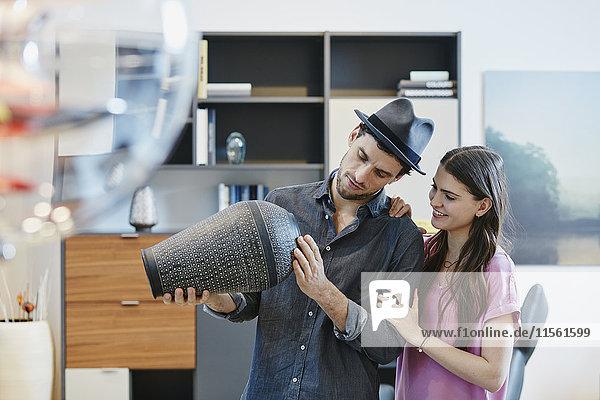 Paar im Möbelhaus mit Blick auf Vase Paar im Möbelhaus mit Blick auf Vase