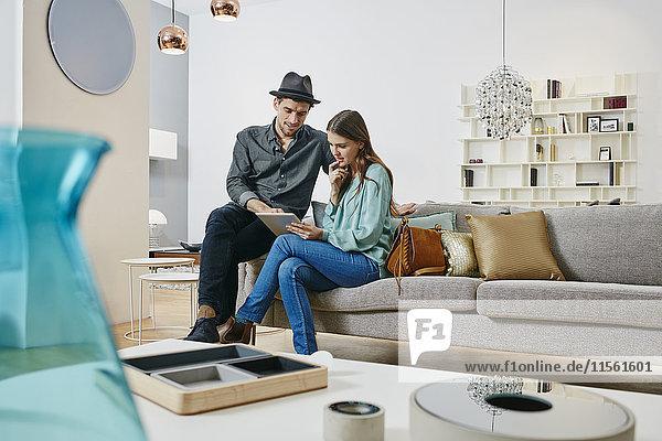 Paar Auswahl von Möbeln im Laden  mit digitalem Tablett Paar Auswahl von Möbeln im Laden, mit digitalem Tablett