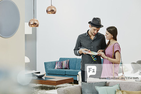 Paar im Möbelhaus beim Betrachten von Farbmustern Paar im Möbelhaus beim Betrachten von Farbmustern