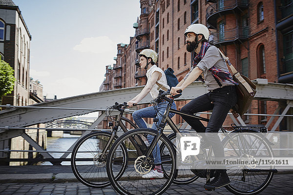 Deutschland  Hamburg  Ehepaar mit Elektrofahrrädern in der Speicherstadt