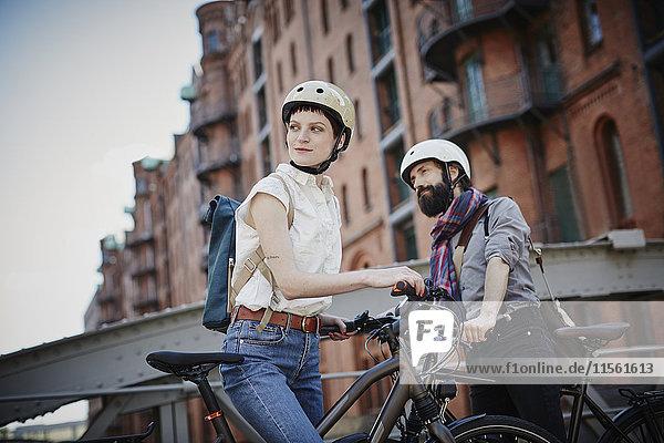 Deutschland  Hamburg  Alte Speicherstadt  Paar mit Elektrofahrrädern wat ching etwas