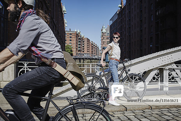 Deutschland  Hamburg  Frau mit Elektrofahrrad  die den vorbeifahrenden Mann auf dem Fahrrad beobachtet.