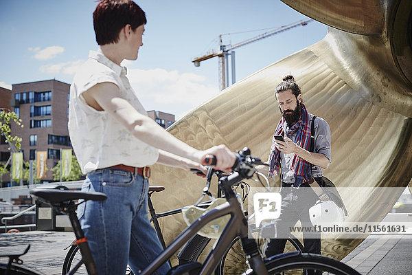 Deutschland  Hamburg  Mann schaut auf das Handy  während die Frau ihn beobachtet.