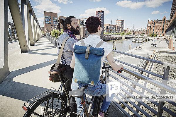 Deutschland  Hamburg  Paar mit Elektrofahrrädern auf einer Brücke