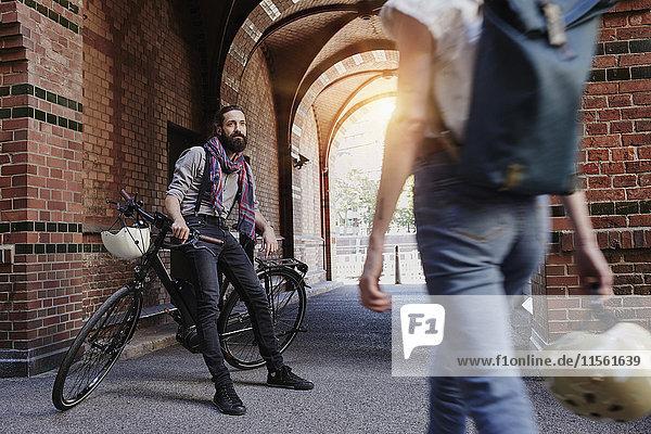 Mann mit Elektrofahrrad beobachtet vorbeifahrende Frau