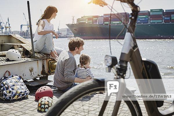 Deutschland  Hamburg  Familie bei einer Radtour an der Elbe beim Beobachten eines Containerschiffes