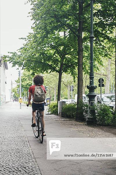 Junger Mann beim Radfahren auf dem Bürgersteig