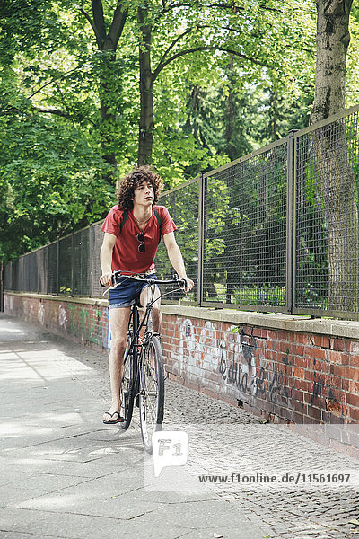Young man riding bicycle on pavement