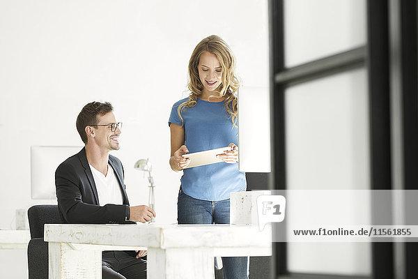 Junger Mann und Frau arbeiten zusammen im Amt
