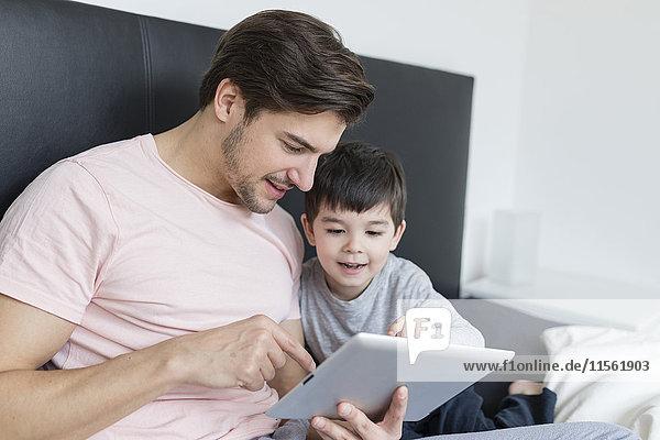 Vater und Sohn schauen auf die Tafel im Bett
