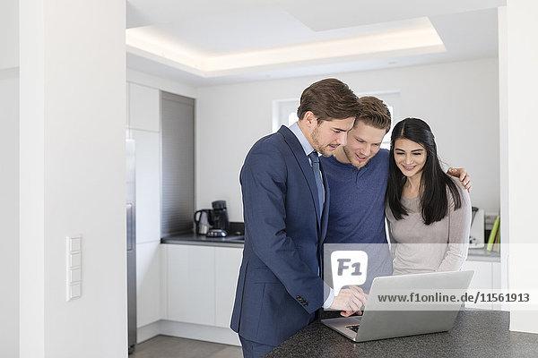 Berater mit Laptop im Gespräch mit dem Paar zu Hause