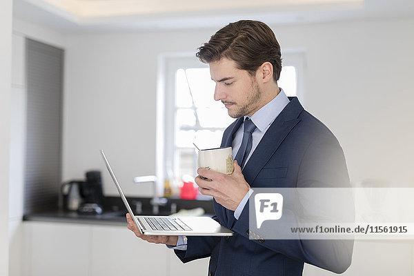 Geschäftsmann zu Hause mit Laptop und Tasse Kaffee