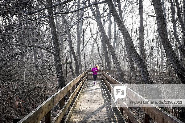 Frau läuft auf Holzbrücke durch den Wald