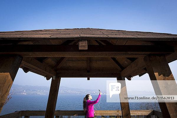 Frau in Sportbekleidung mit einem Selfie auf der Aussichtsterrasse am Meer Frau in Sportbekleidung mit einem Selfie auf der Aussichtsterrasse am Meer