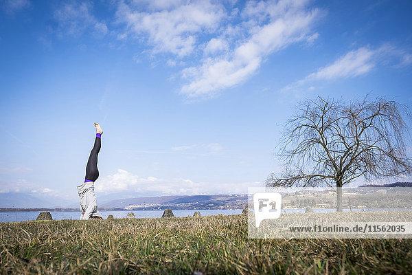 Frau  die Yoga praktiziert und einen Kopfstand am See macht. Frau, die Yoga praktiziert und einen Kopfstand am See macht.