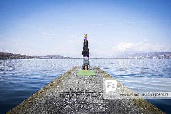 Frau  die Yoga praktiziert und einen Kopfstand auf einem Pier am See macht.