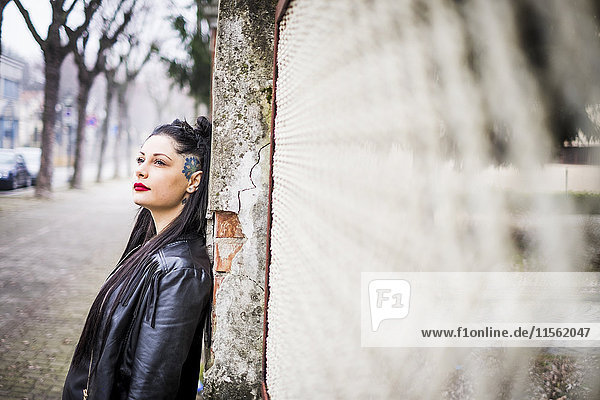 Tagträumende junge Frau an der Wand lehnend