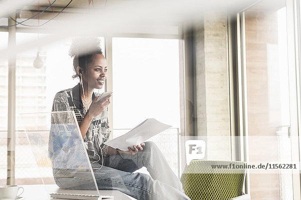 Junge Frau arbeitet im Büro mit transparentem Computer