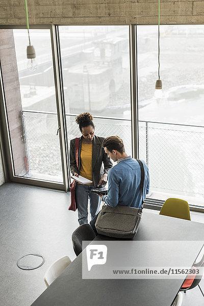 Junge Geschäftsleute diskutieren über Akten im Büro