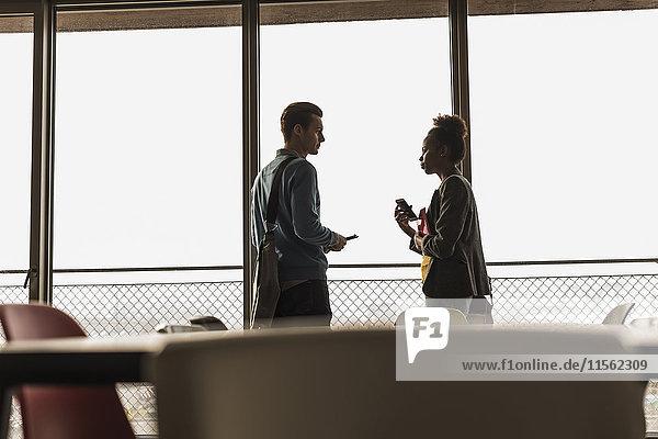 Zwei Kollegen im Büro stehen am Fenster.