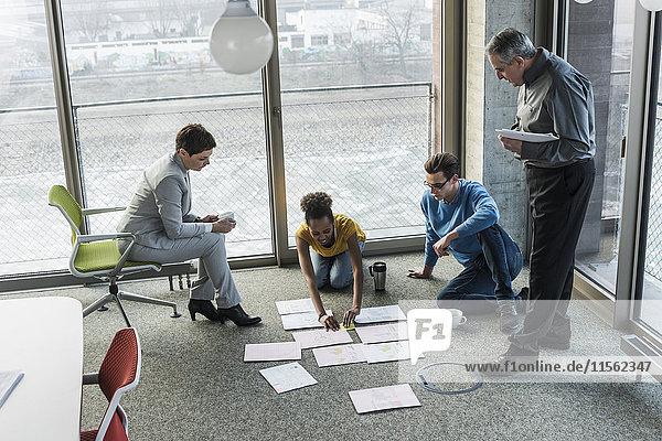 Geschäftsleute  die sich Dokumente auf der Büroetage ansehen.