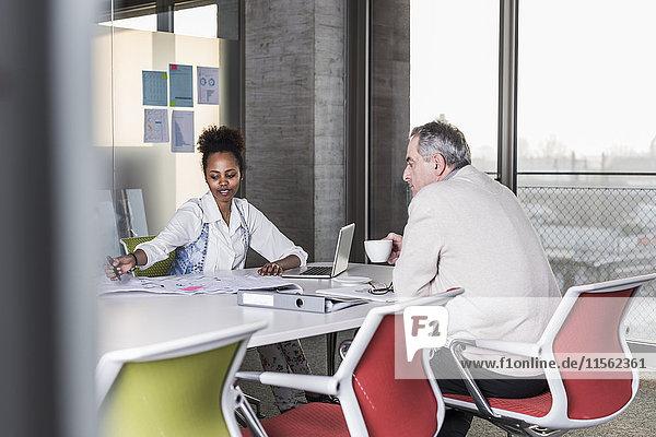 Geschäftsmann und junge Frau beim Gespräch im Konferenzraum