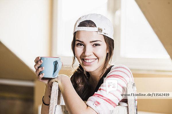 Junge Frau auf der Baustelle mit einer Tasse Kaffee