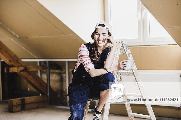 Junge Frau auf der Baustelle ihres neuen Heims  mit einem