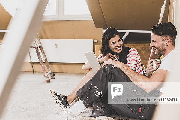 Junges Paar auf der Baustelle seines neuen Zuhauses mit Hilfe eines digitalen Tabletts
