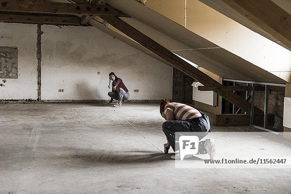 Junger Mann und junge Frau messen Boden auf der Baustelle