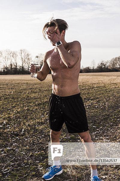 Barechested Athlet in der ländlichen Landschaft gießt Wasser über sein Gesicht
