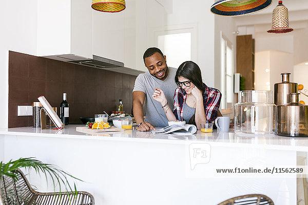Junges Paar beim Frühstück in der Küche und Lesemagazin
