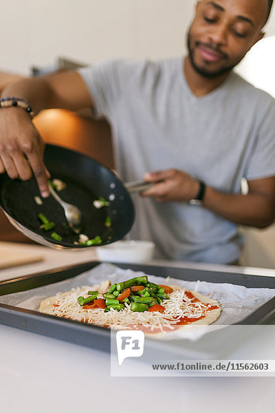 Young couple baking pizza at home