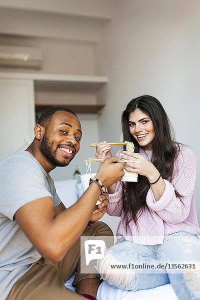 Ein Paar sitzt auf dem Bett und isst chinesische Nudeln.